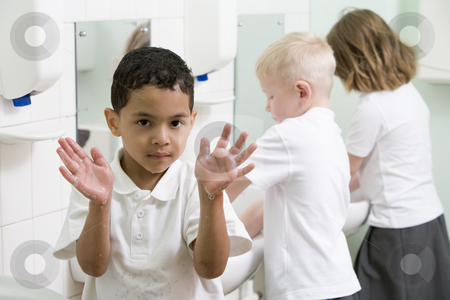 A boy displaying his hands in a primary school bathroom stock photo,  by Monkey Business Images