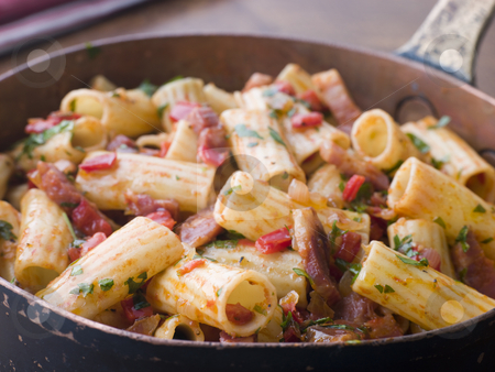 Pan of Rigatoni Pasta with Tomato and Pancetta Sauce stock photo,  by Monkey Business Images