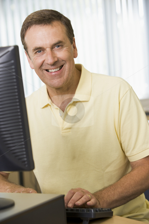 Middle aged man working on a computer stock photo,  by Monkey Business Images