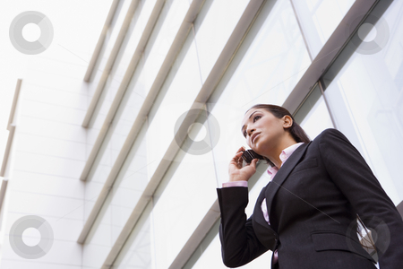 Businesswoman talking on cell phone  stock photo, Businesswoman talking on cell phone outside modern office by Monkey Business Images