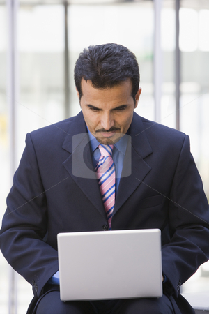 Businessman using laptop computer outside stock photo, Businessman using laptop computer outside office by Monkey Business Images