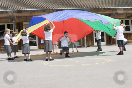 Young children playing with a parachute in a playground stock photo,  by Monkey Business Images