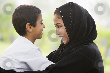 A Middle Eastern woman and her son sitting in a park stock photo,  by Monkey Business Images