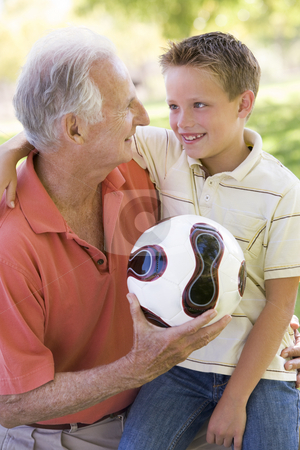 Grandfather and grandson outdoors with ball smiling stock photo,  by Monkey Business Images