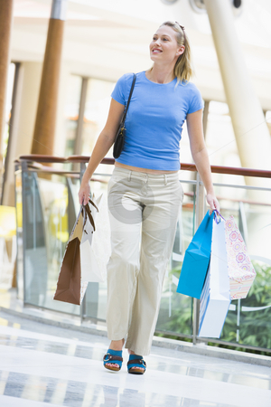 Young woman shopping in mall stock photo, Young woman shopping in mall carrying bags by Monkey Business Images