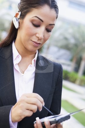 Businesswoman using PDA and earpiece stock photo, Businesswoman using PDA and earpice outside by Monkey Business Images