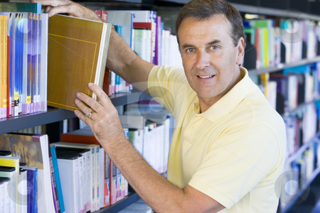 Man pulling a library book off shelf stock photo,  by Monkey Business Images