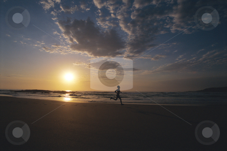 Person running along beach at sunset stock photo,  by Monkey Business Images