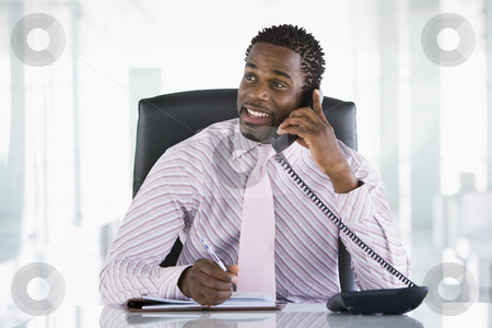 Businessman sitting in office with personal organizer open on te stock photo,  by Monkey Business Images