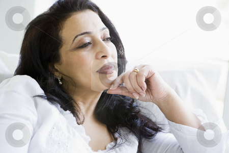 A Middle Eastern woman sitting at home stock photo,  by Monkey Business Images