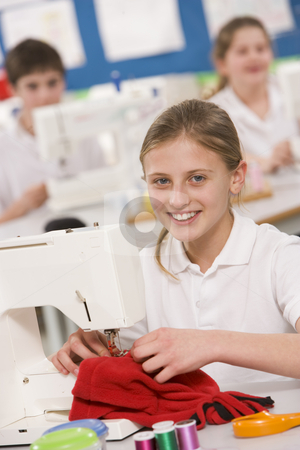 Schoolgirl using a sewing machine in sewing class stock photo,  by Monkey Business Images