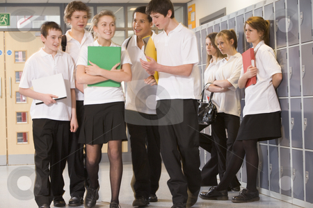 Teenage boys clustered around a girl at school stock photo,  by Monkey Business Images