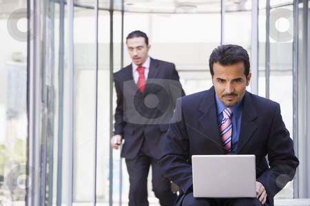 Businessman working at laptop outside stock photo, Businessman working at laptop outside by Monkey Business Images