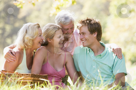 Parents with adult children on picnic stock photo,  by Monkey Business Images