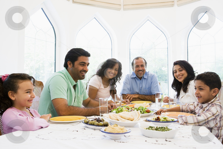A Middle Eastern family enjoying a meal together stock photo,  by Monkey Business Images