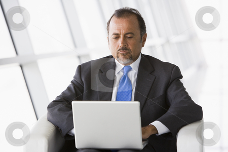 Businessman working on laptop in lobby stock photo, Businessman working on laptop in office lobby by Monkey Business Images