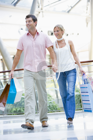 Couple shopping in mall stock photo, Couple shopping in mall carrying bags by Monkey Business Images