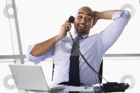 Businessman taking phone call stock photo, Businessman taking call in office by Monkey Business Images