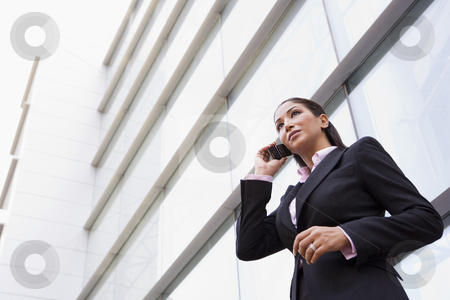 Businesswoman talking on cell phone outside stock photo, Businesswoman talking on cell phone outside modern office building by Monkey Business Images