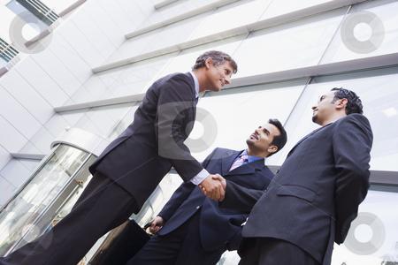 Group of businessmen shaking hands outside office stock photo, Group of businessmen shaking hands outside modern office by Monkey Business Images