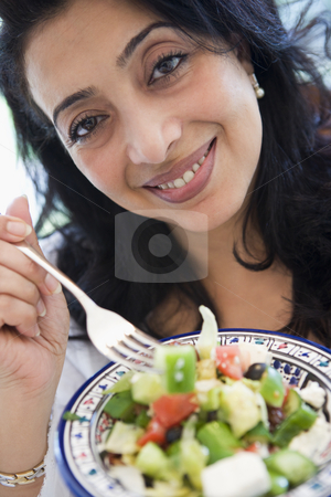 A Middle Eastern woman holding a salad up to the camera stock photo,  by Monkey Business Images