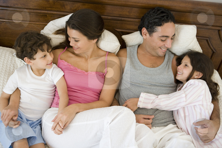 A Middle Eastern family lying on a bed stock photo,  by Monkey Business Images