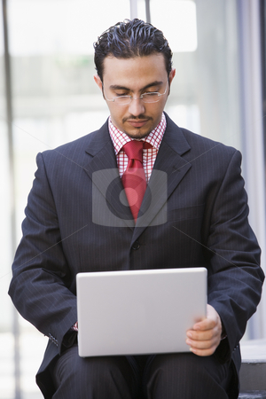 Businessman using laptop outside stock photo, Businessman using laptop outside office by Monkey Business Images