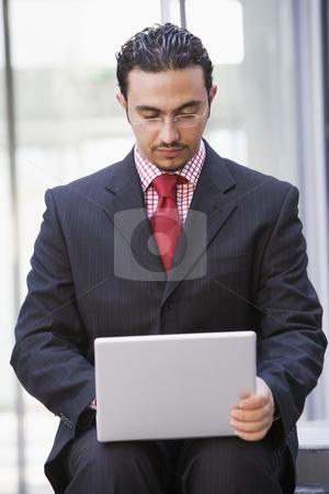 Businessman using laptop outside stock photo, Businessman using laptop outside office by Monkey Business Images