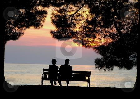 Elderly couple enjoying seaside sunset stock photo, Silhouette of elderly couple enjoying the ocean view at sunset. by Jon Hoisaeter
