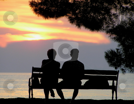 Older couple enjoying sunset view stock photo, Silhouette of older couple enjoying the ocean view at sunset on a warm summer evening. by Jon Hoisaeter