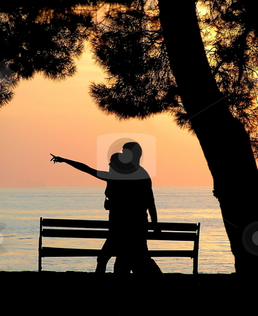 Sunset promenade stock photo, Silhouette of a young couple walking along the seaside at sunset. by Jon Hoisaeter