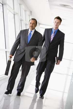 Two businessmen walking through lobby stock photo, Two businessman walking through office lobby by Monkey Business Images