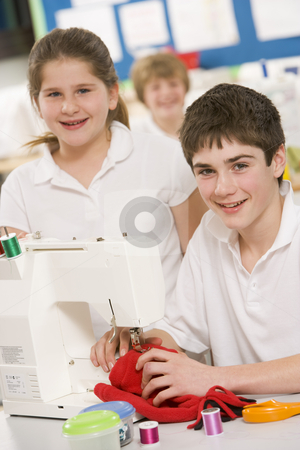 Schoolchildren using a sewing machine in sewing class stock photo,  by Monkey Business Images