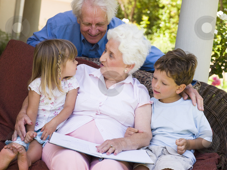 Grandparents reading to grandchildren stock photo,  by Monkey Business Images