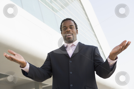 Businessman standing outdoors by building with hands out smiling stock photo,  by Monkey Business Images