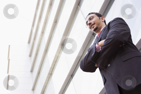 Businessman standing outstanding office stock photo, Businessman standing outside modern office building by Monkey Business Images