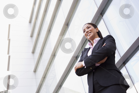 Businesswoman standing outside office building stock photo, Businesswoman standing outside modern office building by Monkey Business Images