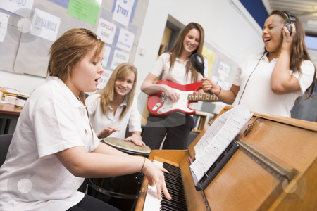 Schoolgirls playing musical instruments in music class stock photo,  by Monkey Business Images