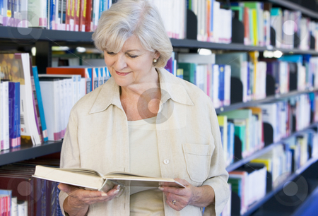 Senior woman reading in a library stock photo,  by Monkey Business Images