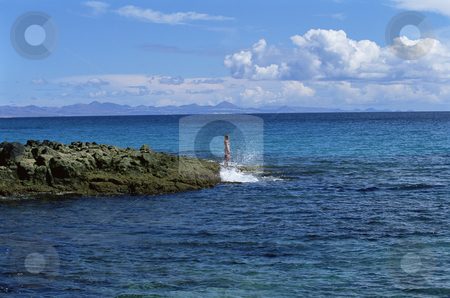 Young woman standing on rocks, looking out to sea stock photo,  by Monkey Business Images