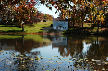 Old house on the pond stock photo, An old house on a small pond during the fall of the year by Tim Markley