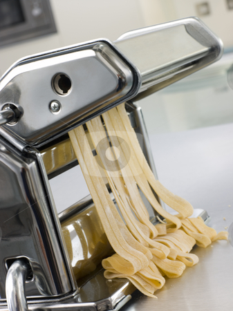 Fresh Egg Tagliatelle Being rolled in a Pasta Machine stock photo, Close up image of Fresh Egg Tagliatelle Being rolled in a Pasta Machine by Monkey Business Images