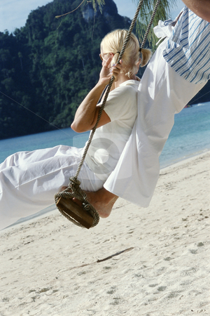 Couple on swing at beach stock photo,  by Monkey Business Images