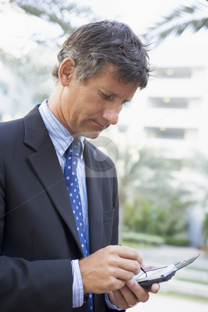 Businessman outdoors using personal digital assistant stock photo,  by Monkey Business Images