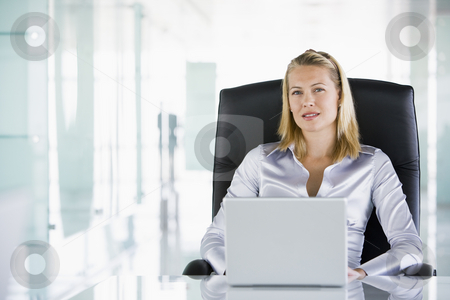 Businesswoman in office with a laptop stock photo,  by Monkey Business Images