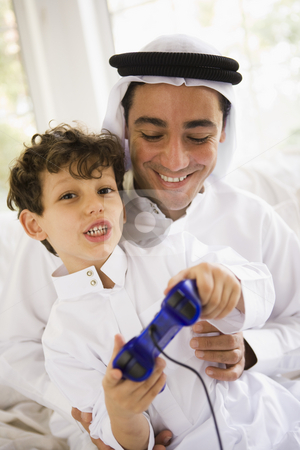 A Middle Eastern father and son playing a video game together stock photo,  by Monkey Business Images