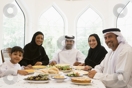 A Middle Eastern family enjoying a meal stock photo,  by Monkey Business Images