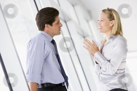 Businessman standing in corridor talking to smiling businesswoma stock photo,  by Monkey Business Images