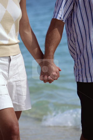 Couple walking on beach holding hands stock photo,  by Monkey Business Images