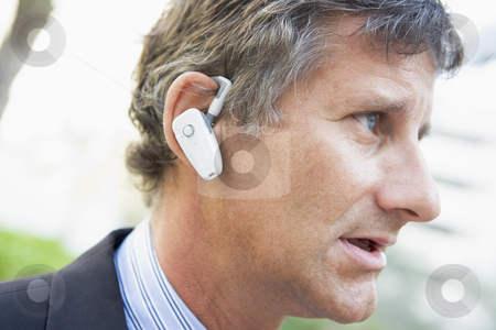 Businessman wearing earpiece outdoors stock photo,  by Monkey Business Images